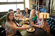 Happy friends with selfie stick at bar or pub Stock Photos