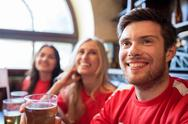Fans or friends watching football at sport bar Stock Photos