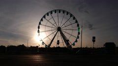Large Ferris wheel slowly turn against evening sky, silhouette view, sun shine Stock Footage