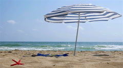 Solitary parasol on the sea beach, slow motion Stock Footage