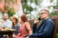 Man with smartphone and friends at summer party Stock Photos