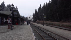 4k Steam locomotive arriving at station winter mountain forest Harz Stock Footage