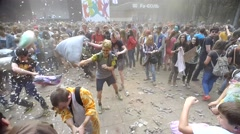 Young people are fighting pillows at event Big Pillows Battle and Holi paints Stock Footage