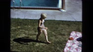 1976: two women sunbathing outdoor on blanket on the grass by the pool.  Stock Footage