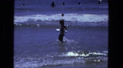 1976: young girl wading out into water with floatation device light waves Stock Footage