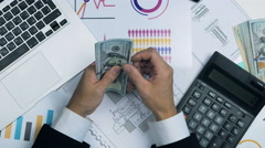 Businessman counting money. Accountant Workplace with laptop, graphs, calculator Stock Footage