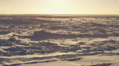 Slow motion - setting sun glare off sea ice with blowing snow Stock Footage