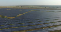 Aerial View. Flying over the solar power plant with sun. Solar panels and sun Stock Footage