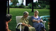 1957: three women talk as they sit in chairs at gathering in yard HICKSVILLE Stock Footage