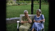 1957: two old women and young woman in meeting of women outdoors, the old women Stock Footage