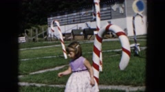 1957: little girls hugs and play around christmas stick. HICKSVILLE, NEW YORK Stock Footage