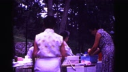 1971: several ladies preparing food at picnic while children and adults play Stock Footage