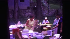 1971: adult women and men with some children in public park at picnic table Stock Footage