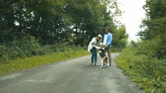 Senior couple with dog on a walk in green summer nature Stock Footage
