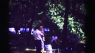 1971: dad carries child through the picnic OMAHA, NEBRASKA Stock Footage