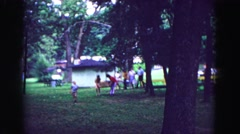 1971: pair lifts cardboard box for outing while children run ahead and others Stock Footage