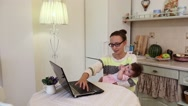 Woman working from home with baby on lap Stock Footage