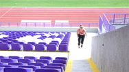 Teenager girl athlete running up the stairs in a stadium Stock Footage