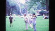 1971: middle-aged woman and older woman take turns throwing large darts in park Stock Footage