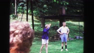 1971: two women and man stand in row while one woman tosses green object OMAHA Stock Footage