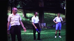 1971: older man throws lawn darts with friends at park OMAHA, NEBRASKA Stock Footage
