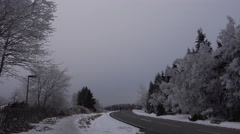 4k Street in snowy Harz mountains with fir trees and driving car Stock Footage