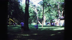 1971: boy with blue ball walking with other kids at recreational area OMAHA Stock Footage