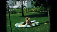 1957: two toddlers play in small inflatable swimming pool HICKSVILLE, NEW YORK Stock Footage
