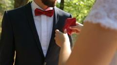 Bride puts handkerchief into groom's suit pocket Stock Footage
