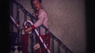 1973: boy in pajamas happily hangs his stocking for santa on christmas eve Stock Footage