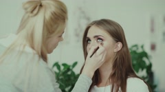 Model looks up, make-up artist paint the lower eyelid using a brush Stock Footage
