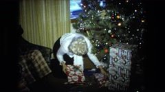 1974: family sorting presents near christmas tree FORT WAYNE, INDIANA Stock Footage