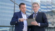 Two businessmen using digital tablet computer touchscreen Stock Footage
