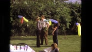1974: family members relax at an outdoor birthday party decorated with balloons Stock Footage