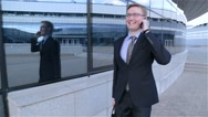 Businessman is walking and talking on the phone (steadicam shot) Stock Footage