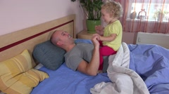 Happy toddler girl riding daddy on bed. Child enjoy time with father Stock Footage