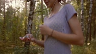 Young attractive woman jogging in the forest listening to her favorite songs Stock Footage