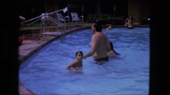 1974: young girl swimming and playing in pool. FORT WAYNE, INDIANA Stock Footage