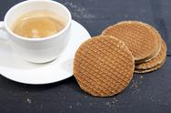 Dutch cookie stroopwafels with cup of coffee on black wooden background Stock Photos