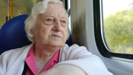 Senior woman looks through the window in a train Stock Footage