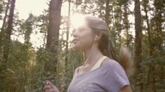 Portrait of young cheerful woman jogging along the forest path Stock Footage
