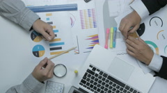Unrecognizable businessmen working together at office desk with financial graphs Stock Footage