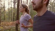 Close-up of young couple jogging together in the forest Stock Footage