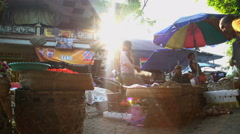 Bali, Indonesia - Sun flare through people shopping for fresh fruit Stock Footage