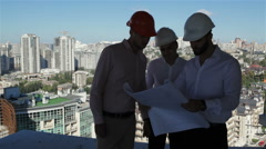 Three builders examine the project of building under construction Stock Footage