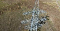AERIAL: Flying up the high voltage electricity tower and power lines. Aerial Stock Footage