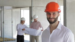 Construction engineer poses at the building under construction Stock Footage