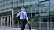 Happy businessman goes for about modern office center Stock Footage