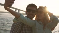 Happy young couple taking photo of themselves against river background Stock Footage