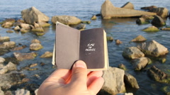 Time to travel idea, hand holding a book with the inscription and rocks on the Stock Footage
